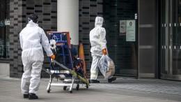Zwei Krankenschwestern in Schutzkleidung auf dem Weg zum Karolinska-Institut Stockholm mit einem Patienten (Foto-Allianz / TT NEWS AGENCY / Anders Wiklund)