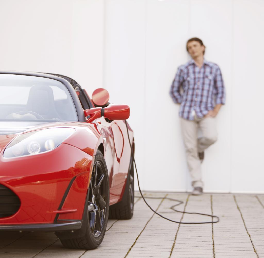 Junger Mann, der sein Elektroauto füllt