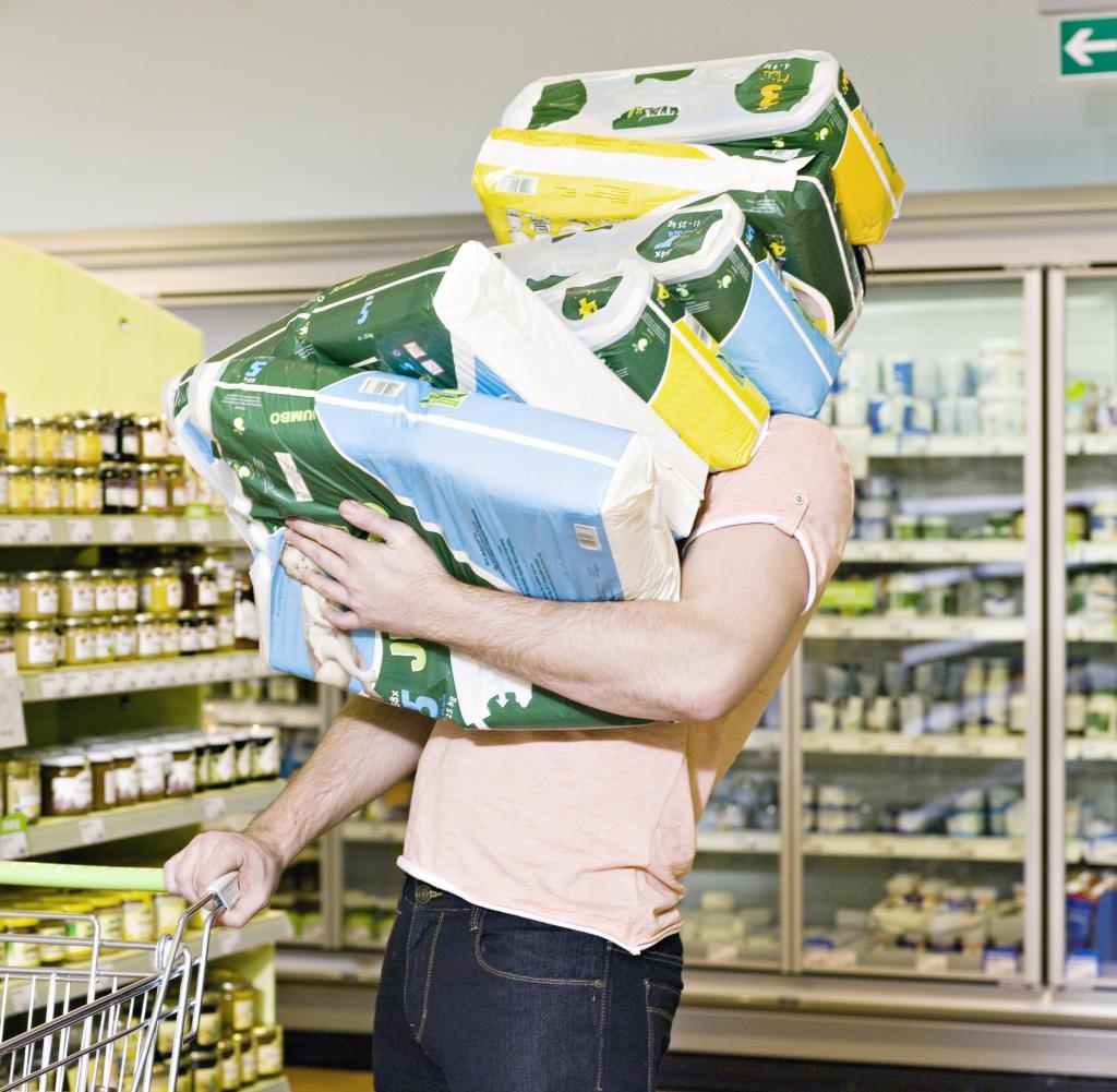 Mann, der Chemikerprodukte im Supermarkt trägt