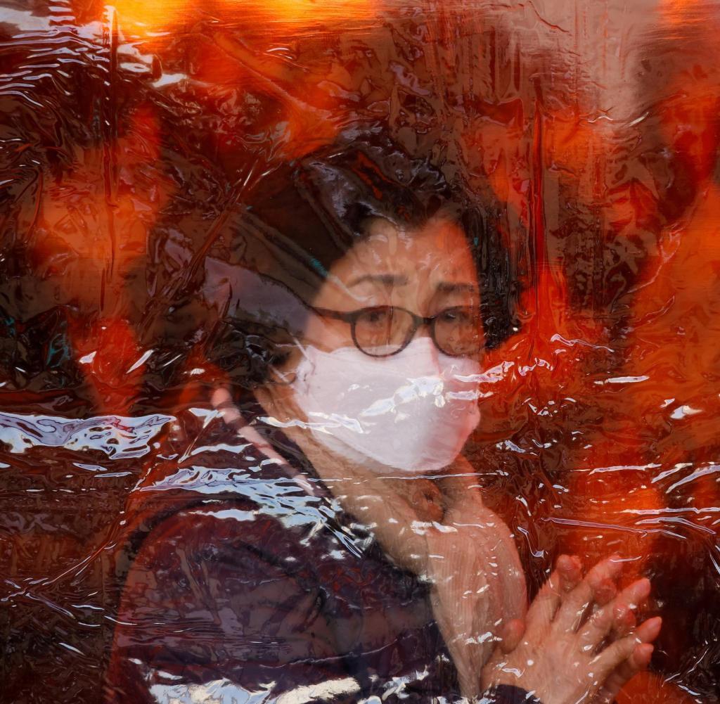 Eine Mutter betet hinter einer Plastikplane in einem buddhistischen Tempel in Seoul für die Gesundheit ihrer Kinder und den Schulerfolg trotz der schwierigen Corona-Zeiten