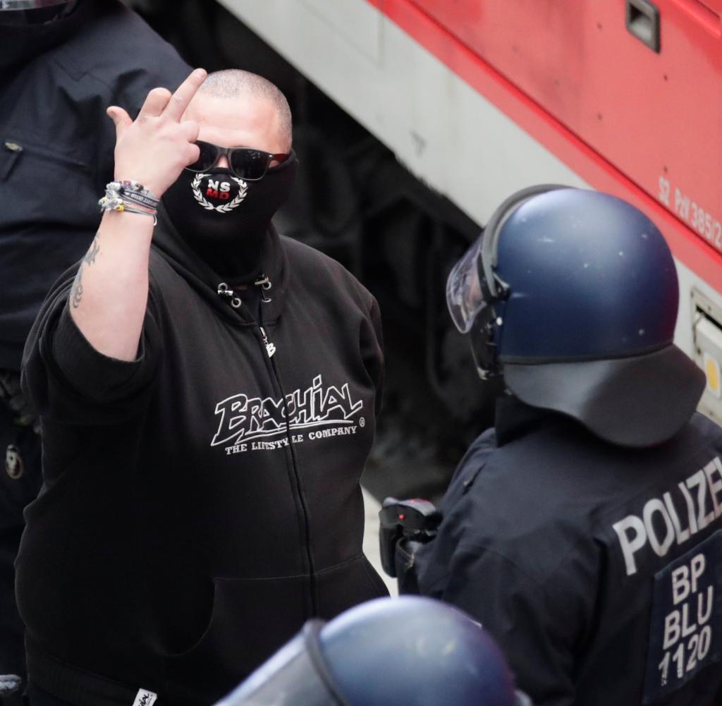 Ein angekommener Mann wird in Dresden eingecheckt - das Symbol auf seiner Maske wird auch von einer Facebook-Gruppe namens genannt