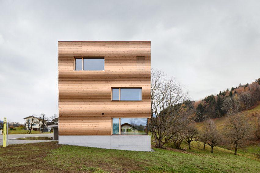 Ein quadratisches Holzhaus mit einem Betonsockel