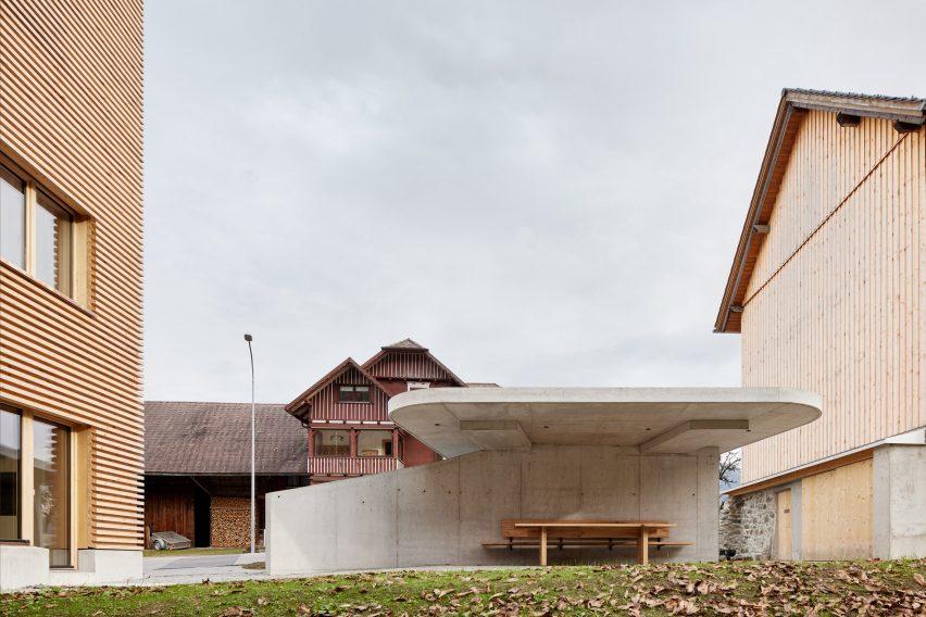 Ein Betoncarport vor einem Holzhaus