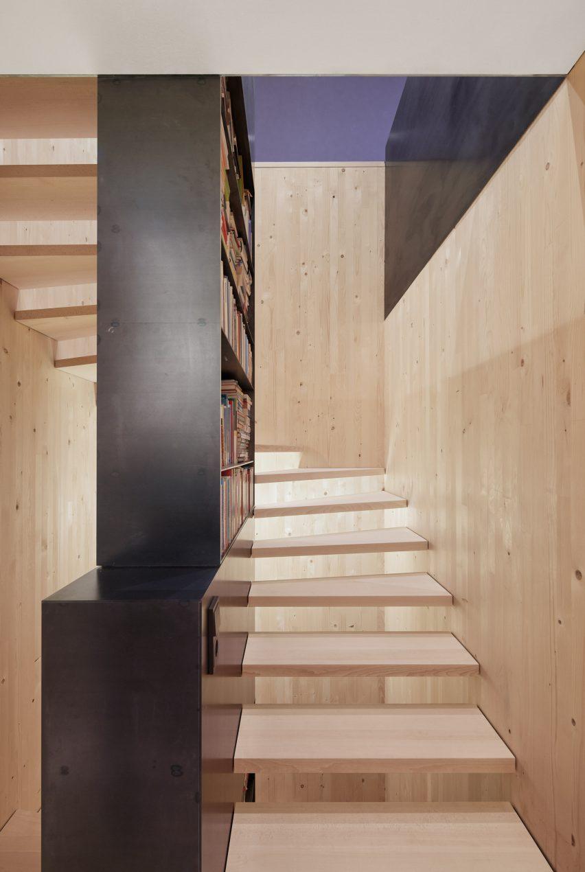 Eine offene Treppe in Fichtendecke mit einem schwarzen Bücherregal aus Stahl