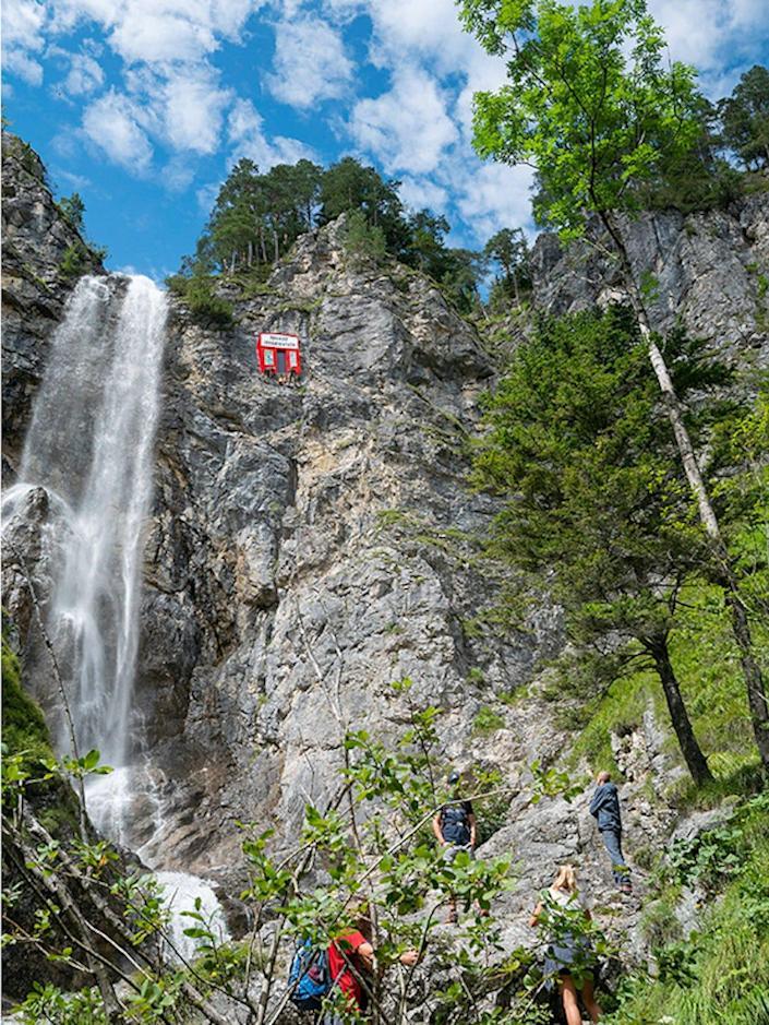 Ein knallrotes Touristenbuch ist in den Fels eines Berges eingebettet.