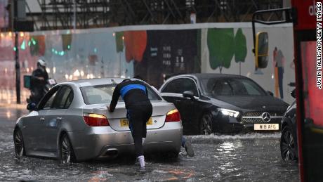 Im Londoner Stadtteil Nine Elms wird ein Auto durch Hochwasser geschoben.