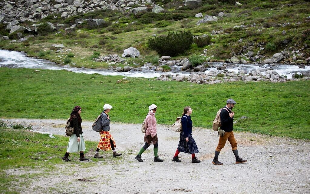 Actors of the theater group Teatro Caprile reenact an emigration scene on the old Roman road on the Windbach Alp in the Krimmler Tauern Alps on the border between Austria and Italy, near Krimml, on June 25, 2021. (ALEX HALADA/AFP)
