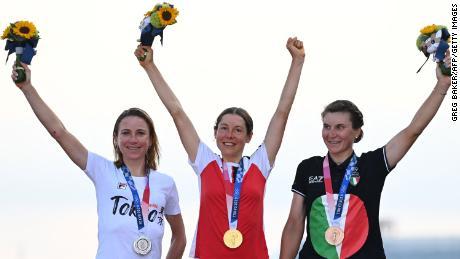 Die niederländische Silbermedaillengewinnerin Annemiek Van Vleuten (links), die österreichische Goldmedaillengewinnerin Anna Kiesenhofer (Mitte) und die italienische Bronzemedaillengewinnerin Elisa Longo Borghini (rechts) feiern bei der Siegerehrung für das Straßenrennen der Frauen auf dem Podium.