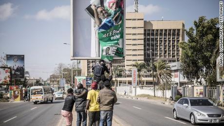 Anhänger des designierten sambischen Präsidenten der oppositionellen United Party for National Development (UPND) Hakainde Hichilema entfernen am 16. August 2021 ein Plakat des ehemaligen Präsidenten Edgar Lungu von einem Posten in Lusaka.