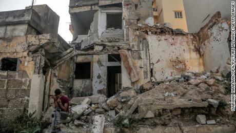 Ein Mann sitzt fast ein Jahr nach der Explosion in den Trümmern eines zerstörten Hauses in der Nähe des Hafens.