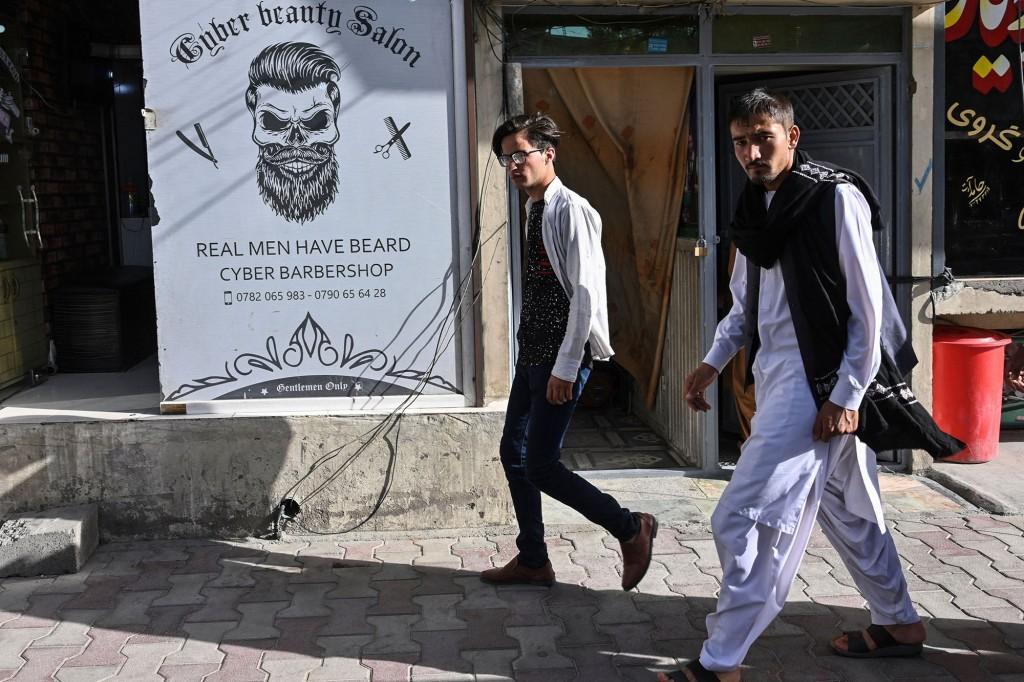Männer gehen an einem Friseursalon in Kabul vorbei.