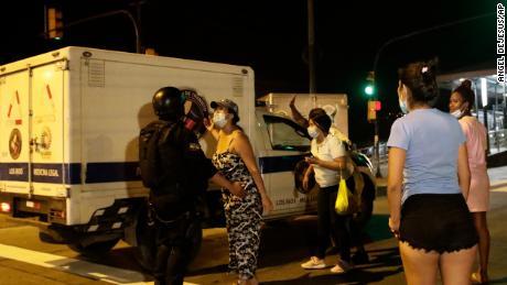 Verwandte von Insassen warten auf Neuigkeiten, als ein Lastwagen der Gerichtsmediziner nach einem Aufstand in Guayaquil, Ecuador, am Dienstag, den 28.