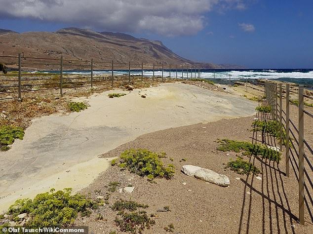 Abgebildet ist eine Felsplatte mit den Fußabdrücken in der Nähe von Trachilos mit Blick auf das Mittelmeer